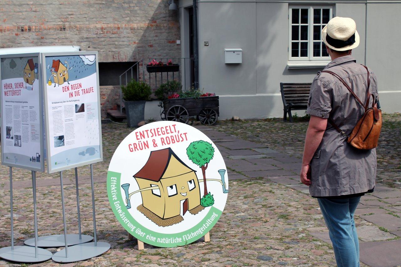"""Eine Besucherin betrachtet ein Poster der Ausstellung """"Mein Haus sicher bei Wind und Wetter"""", die hilfreiche Tipps zum Umgang mit Regenwasser bietet."""