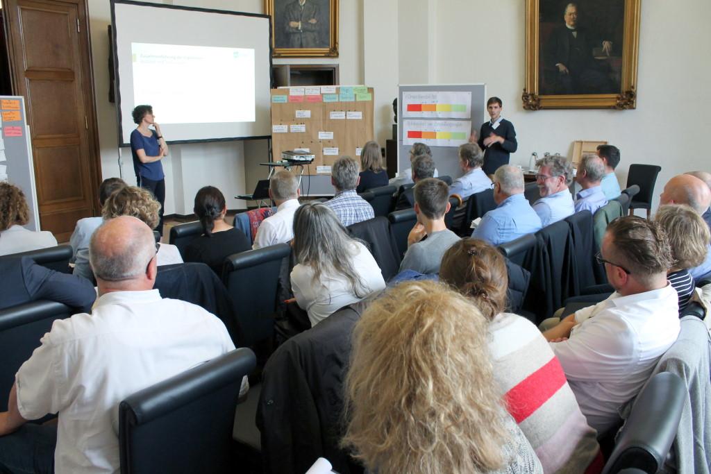 Die Teilnehmenden des Workshops hören sich die Zusammenfassung der Ergebnisse aus den Arbeitsgruppen an.
